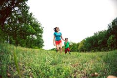 A woman and her son are running along the grass. A women and her son are running along the green grass. Mom holds the child by the hand and laughs. A boy is Stock Photos