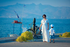 Woman and her son talking on jetty by the sea Stock Images