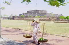 Woman with her stockade. Past the citadel in Hue. She wears a traditional silk dress which is locally called Pajamas.  Its conical hat that protects from the Royalty Free Stock Photo