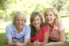 Woman And Her Teenage Children Lying On Grass Stock Photo