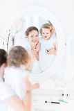 Woman and her toddler daughter applying make up Royalty Free Stock Image