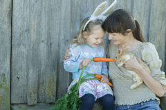 Woman with her toddler daughter feeding domestic little Easter rabbit Stock Photos