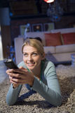 A woman with her TV remote Stock Photography