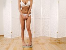 Woman in her underwear checking her weight Royalty Free Stock Photos