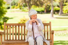 Woman with her walking stick in the park Stock Images
