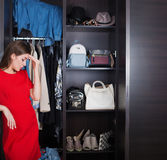 Woman and her wardrobe. Pretty young woman choosing clothing from the wardrobe royalty free stock photography