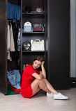 Woman and her wardrobe. Pretty young woman choosing clothing from the wardrobe royalty free stock image