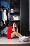Woman and her wardrobe. Pretty young woman choosing clothing from the wardrobe stock images