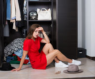 Woman and her wardrobe. Pretty young woman choosing clothing from the wardrobe royalty free stock images