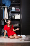 Woman and her wardrobe. Pretty young woman choosing clothing from the wardrobe stock photo