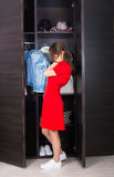 Woman and her wardrobe. Pretty young woman choosing clothing from her closet stock image