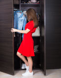 Woman and her wardrobe. Pretty young woman choosing clothing from her closet royalty free stock images