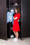 Woman and her wardrobe. Pretty young woman choosing clothing from her closet royalty free stock photo