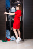 Woman and her wardrobe. Pretty young woman choosing clothing from her closet royalty free stock photography