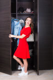Woman and her wardrobe. Pretty young woman choosing clothing from her closet royalty free stock photos