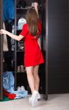 Woman and her wardrobe. Pretty young woman choosing clothing from her closet stock photography