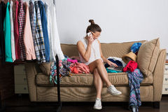 Woman and her wardrobe. Young hipster woman sorting her wardrobe Stock Images