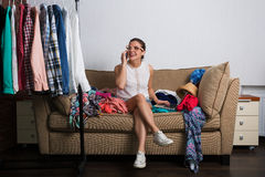Woman and her wardrobe. Young hipster woman sorting her wardrobe Stock Photo
