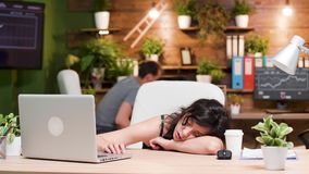 Woman at her workplace sleeps while her colleague is working stock footage
