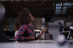 Woman at her workplace in startup business office listening musi. Young black woman at her workplace in startup business office listening music on headphones and Stock Images