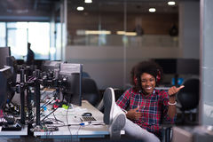 Woman at her workplace in startup business office listening musi. Young black woman at her workplace in startup business office listening music on headphones and Stock Photo