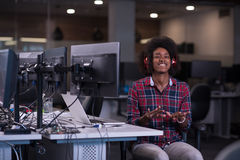 Woman at her workplace in startup business office listening musi. Young black woman at her workplace in startup business office listening music on headphones and Stock Photos