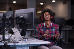 Woman at her workplace in startup business office listening musi. Young black woman at her workplace in startup business office listening music on headphones and Royalty Free Stock Photography
