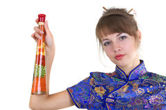 Woman with herbs. Young woman in Chinese dress with herbs in bottle Royalty Free Stock Photos