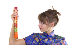 Woman with herbs. Young woman in Chinese dress with herbs in bottle Royalty Free Stock Photo
