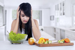 Woman hesitate to eat salad Royalty Free Stock Photography
