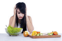 Woman hesitate to eat salad 1 Stock Photo