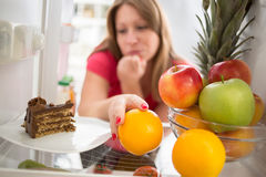 Woman hesitating whether to eat cake or orange Stock Images