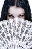 Woman hidden behind a fan. Woman - fortune-teller - hidden behind a white fan Royalty Free Stock Image