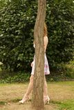 Woman hides behind a tree Royalty Free Stock Images