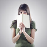 Woman hides behind a book Royalty Free Stock Photo