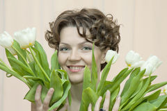 Woman hides behind a bouquet of white tulips Stock Image