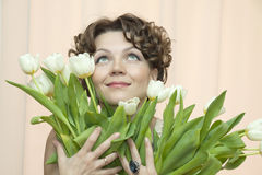 Woman hides behind a bouquet of white tulips Stock Photo
