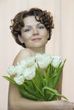 Woman hides behind a bouquet of white tulips Stock Photography
