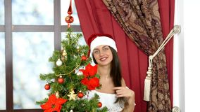 Woman hides behind the Christmas tree stock video footage