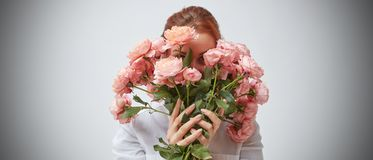 Bouquet of beautiful roses in the hands of a girl. A woman hides her face behind a bouquet of pink roses. St. Valentine`s Day. Women`s Day stock photo