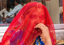 Woman hides her face with red veil. Royalty Free Stock Images