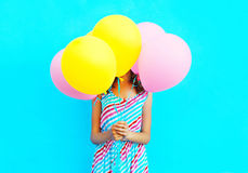 Woman is hides her head an air colorful balloons having fun. Over a blue background Stock Photo