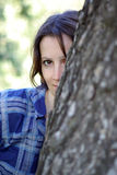Woman hides from a tree Royalty Free Stock Photography