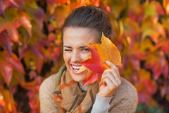 Woman hiding behind autumn leafs. Portrait of happy young woman hiding behind autumn leafs in front of foliage Royalty Free Stock Photos