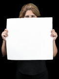 Woman hiding behind a banner with space for text. Woman hiding behind a white banner with space for text (isolated on black Stock Photo