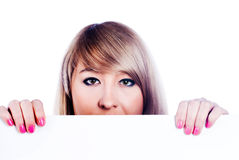 Woman  hiding behind billboard. Young woman hiding behind a billboard and looking on camera  on white background Royalty Free Stock Photos