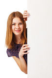 Woman Hiding Behind the Billboard. Young woman appear from the side of the billboard Stock Image