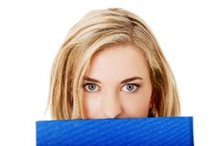 Woman hiding behind a binder Royalty Free Stock Photos
