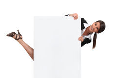 Woman hiding behind blank board. Cheeky young woman in suit hiding behind blank board Stock Photos