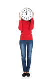 Woman hiding behind a clock. Stock Photos